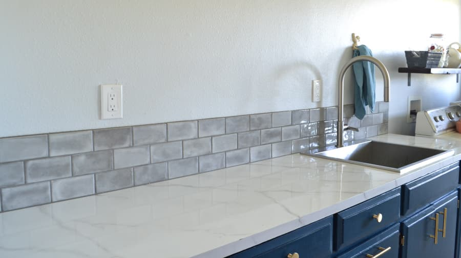 A grey tiled backsplash with a white marble countertop and a stainless steal faucet on the right