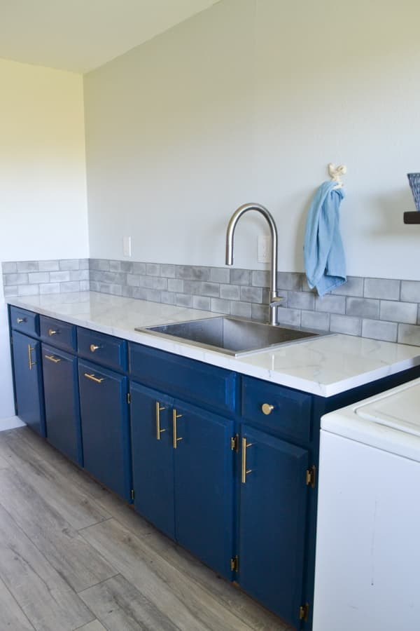 Blue cabinets in a laundry room with gold hardware, a white marble countertop with a grey subway tile backsplash and a stainless steel sink and facuet with a blue towel hanging to the right of the faucet