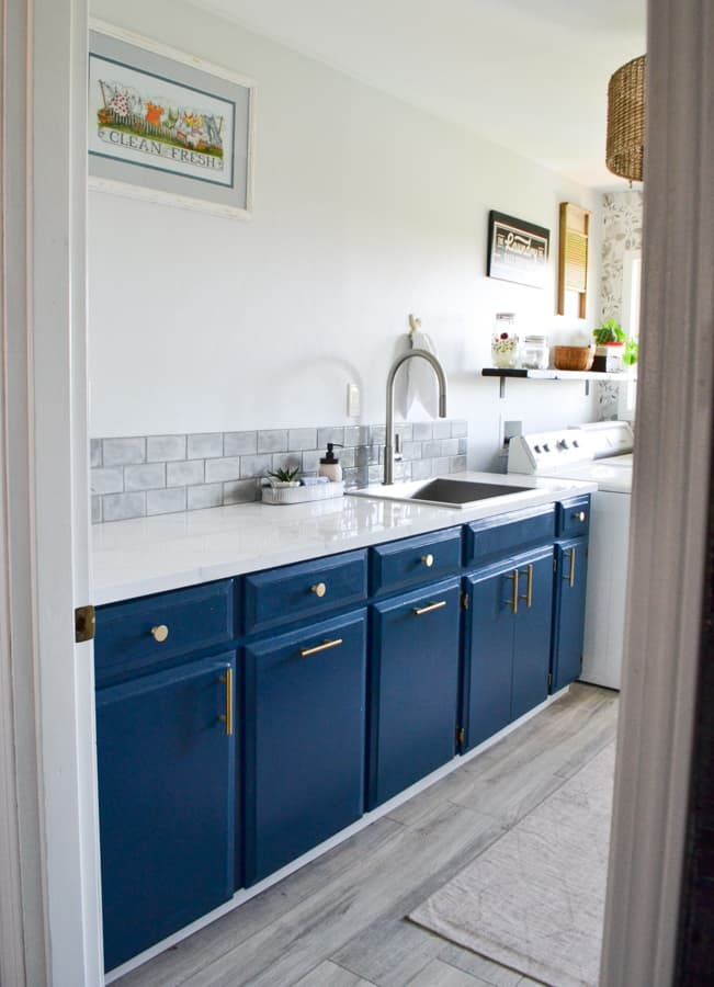 A side view of a laundry room with blue cabinets, white marble countertops, a gray backsplash and a new sink and faucet