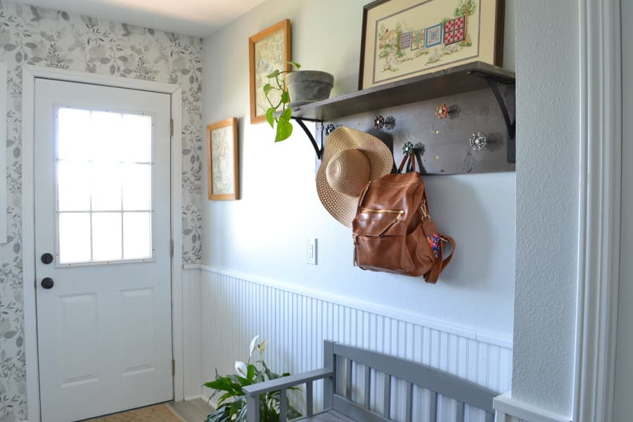 Looking towards an exterior door with a wall to the right with a coat hook and needlepoint on the wall and a grey bench below with white wainscotting on half the wall