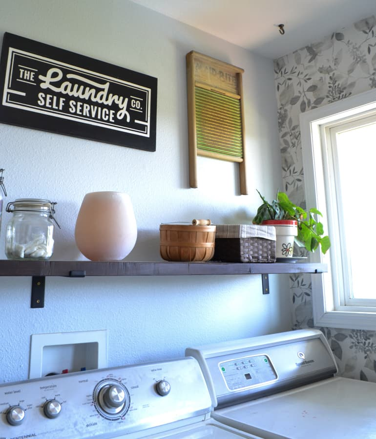 A view above a washer and ryer to show a shelf and a laundry room sign and a vintage washboard hung on the wall with a window to the right