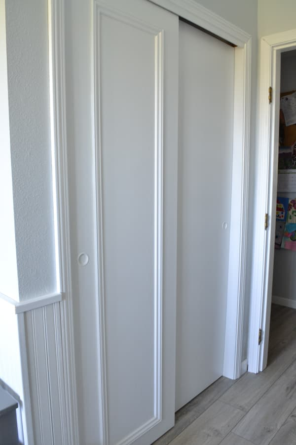 A view of white painted closet doors with trim added to one