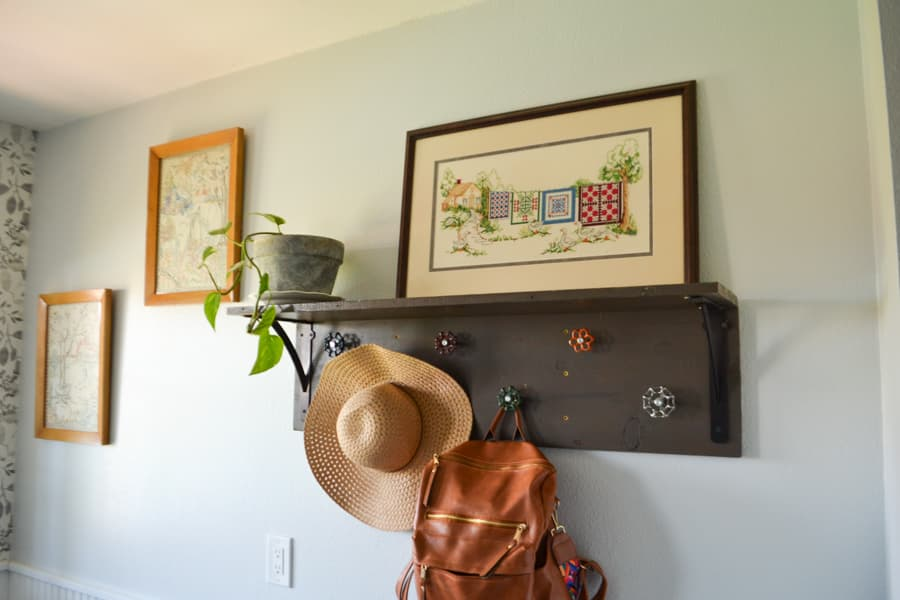 A coat rack with a woman's brimmed hat hanging along with a brown leather backpack with a plant sitting on top the coat rack and a cross stitch of quilts hanging next to the plant