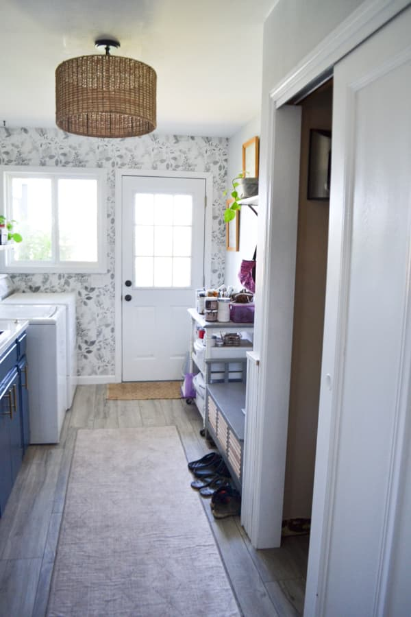 A view into a laundry room with shoes on the floor and a craft cart next to the door