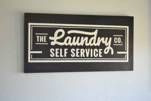 A close up of a black sign with white lettering hanging in a laundry room