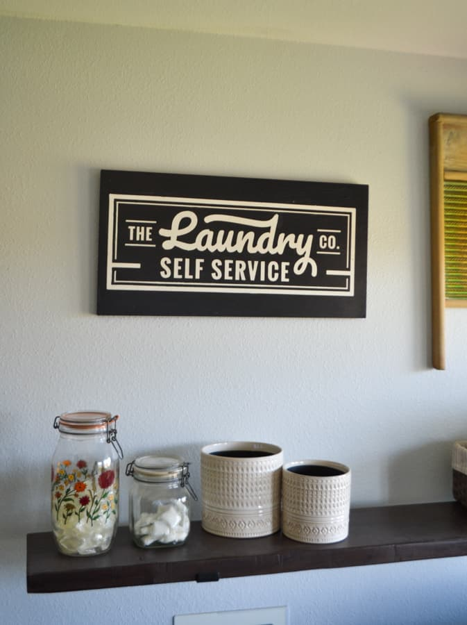 A laundry sign with white lettering on black hanging above a shelf above a washing machine