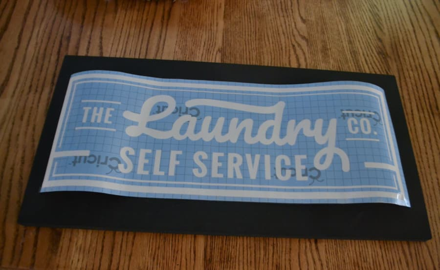 An above view of a black sign with a blue laundry self service stencil