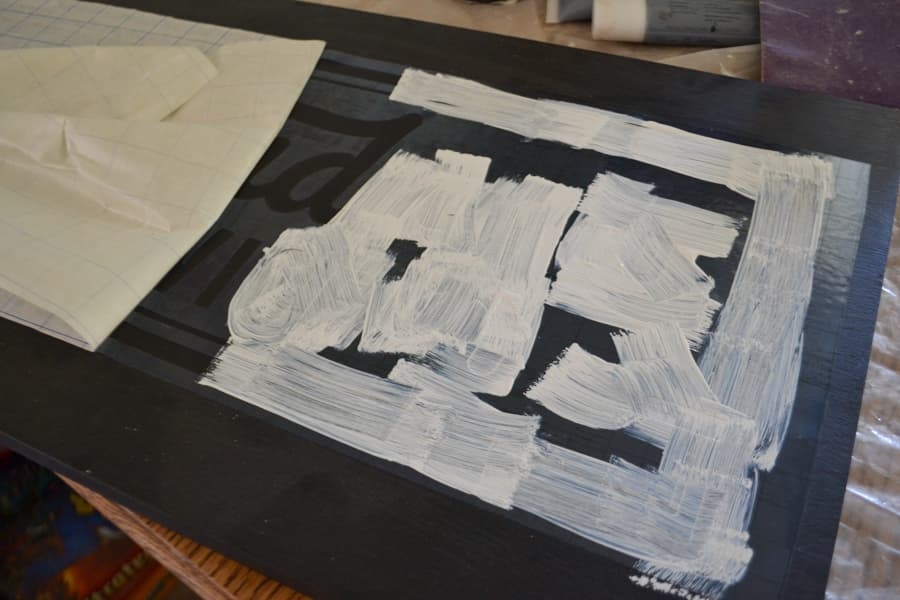 An above view of a stencil with white paint over the stencil on a black surface