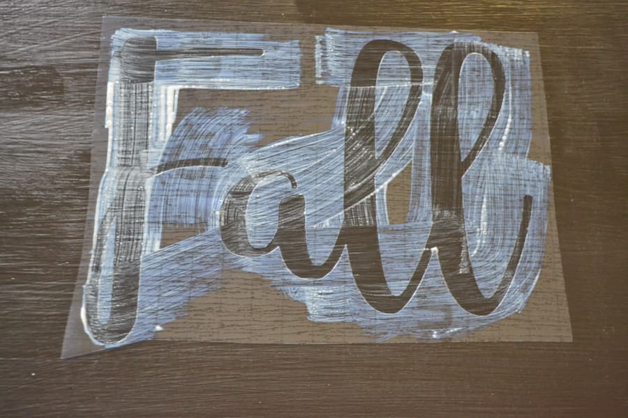 """A close up of a """"Fall"""" wording stencil with Mod Podge applied over top"""