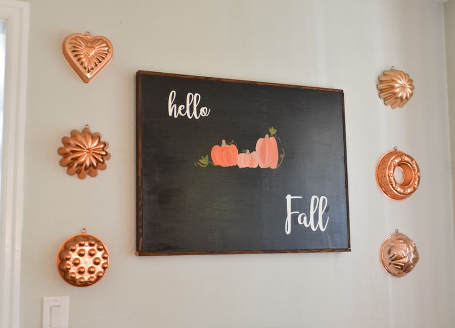 A large black sign with the words hello fall in white and orange pumpkins painted in the middle with copper molds hanging on the sides next to the sign