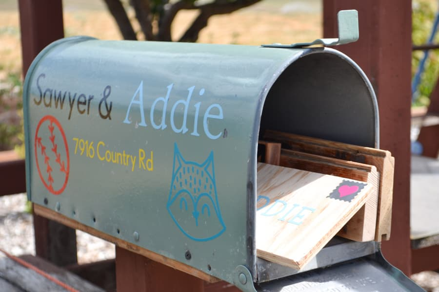 A close up of an open mailbox with wood mail sticking out