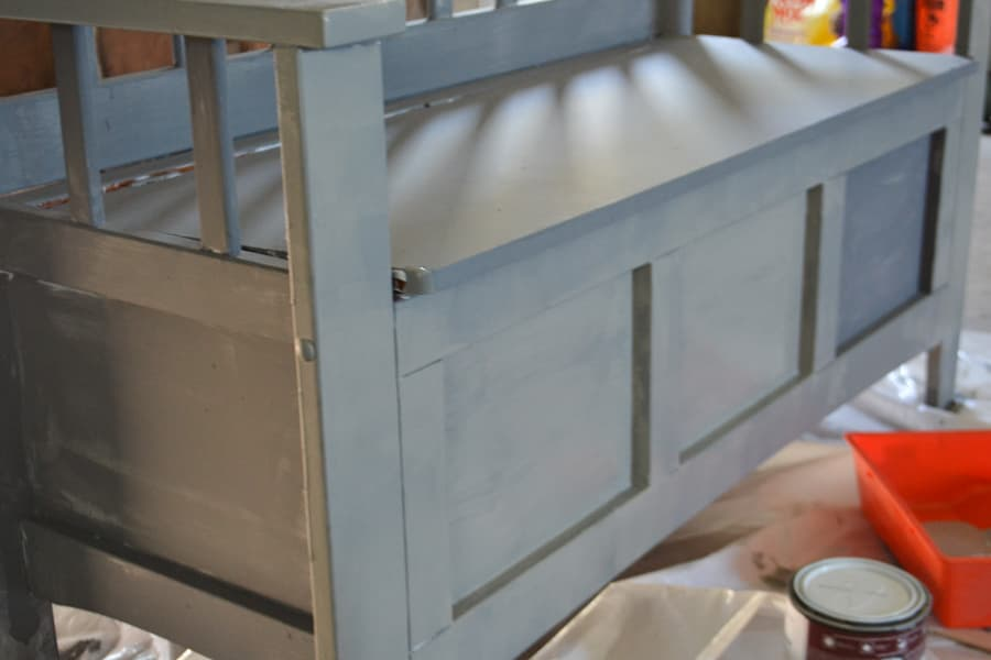 A close up photo of a gray painted shoe bench