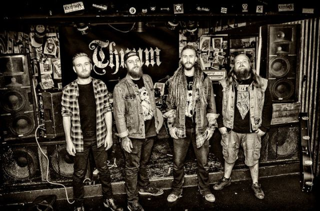 Black and white photo of the band standing in front of a stage