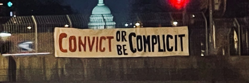 convict or be complicit banner near the capitol