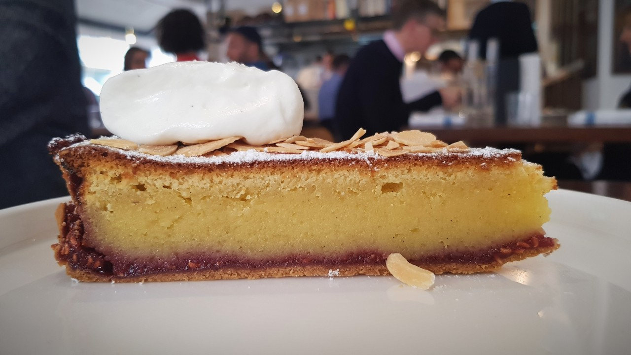 A bakewell tart of jam and almonds garnished with a dollop of thick cream