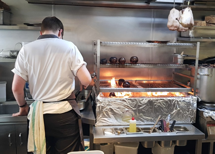 The kitchen at Clipstone London where ducks roast over a fire and chefs are busy at work