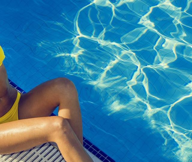 Woman In Yellow Bikini Lounging By The Pool In Sunhat