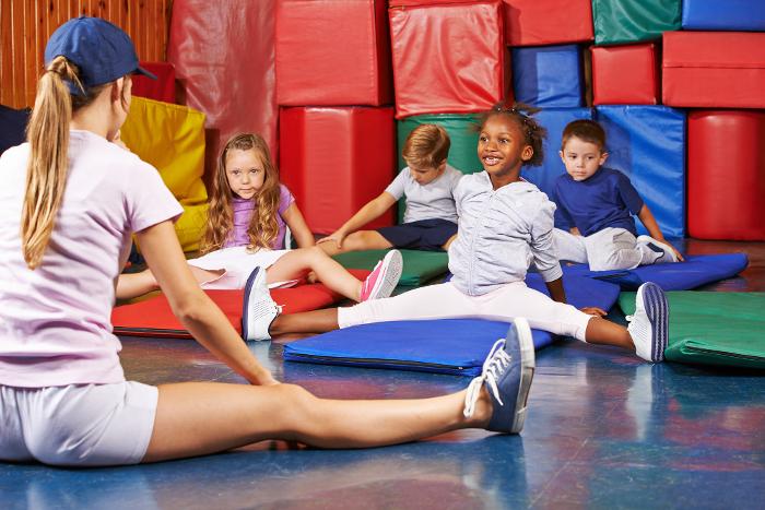 Kinder turnen beim Kindersport im Kindergarten zusammen mit der Erzieherin