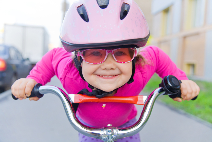 little girl in  helmet and goggles riding  bicycle