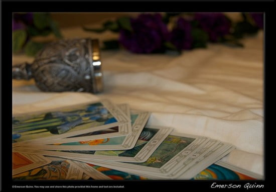 Tarot cards and gothic pewter goblet rest on bed