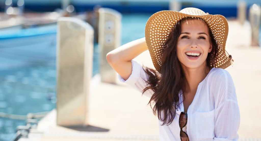 happy smiling woman on pier in sunhat