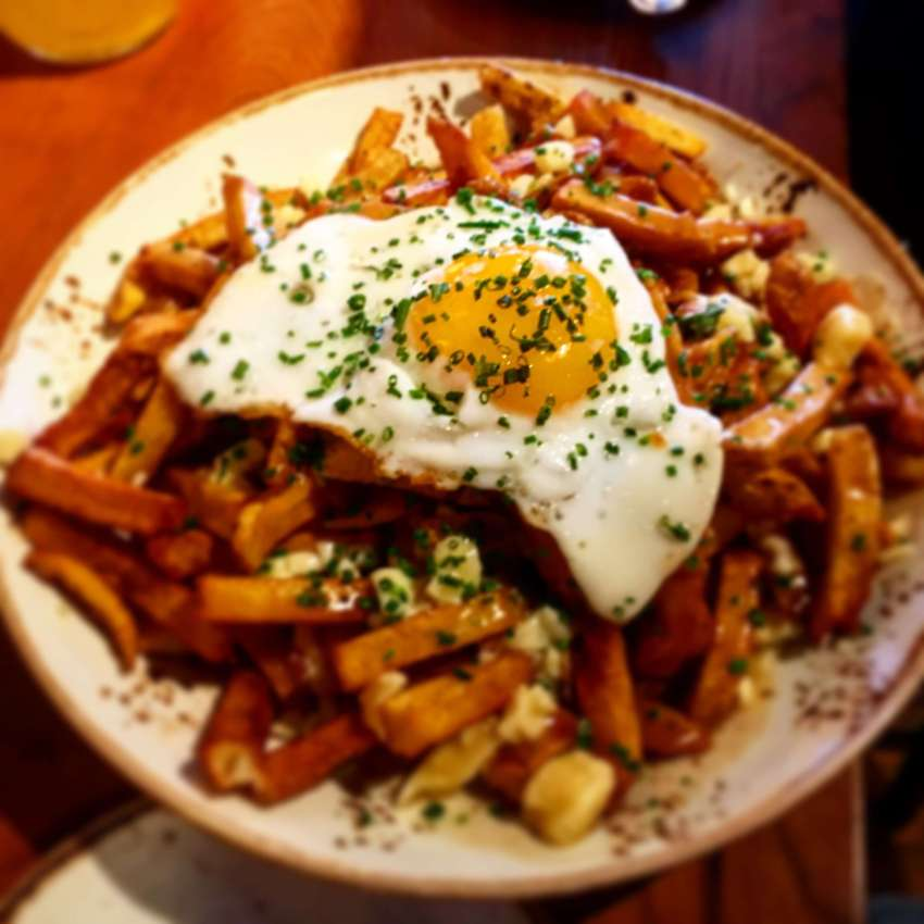 poutine with fried egg at Duckfat is delicious and a classic part of Portland's food scene.