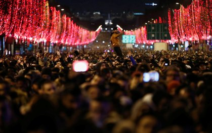 People gather on the Champs Elysees during the New Year's celebrations near the Arc de Triomphe in Paris