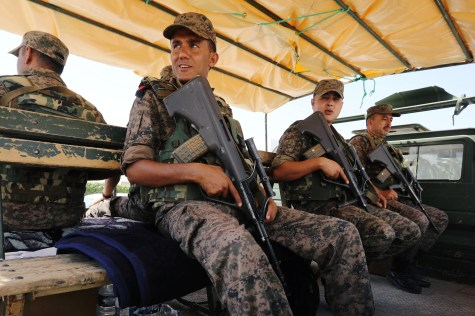 Army soldiers sit on a truck outside a sports hall where ballot boxes and election material are collected to be distributed to polling stations in Tunis