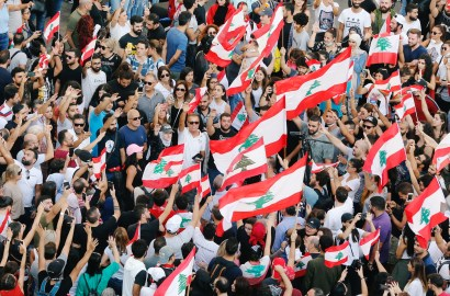Demonstrators carry national flags and gesture during an anti-government protest in Beirut
