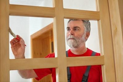 Home renovation, worker painting wooden door, varnishing