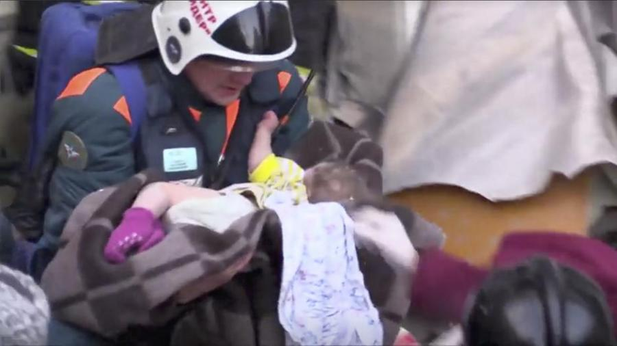 A still image taken from a video footage showsaA rescuer carries a 10-month-old child found alive in the rubble of a Russian apartment block that partially collapsed after a suspected gas blast in Magnitogorsk | Autor: HANDOUT
