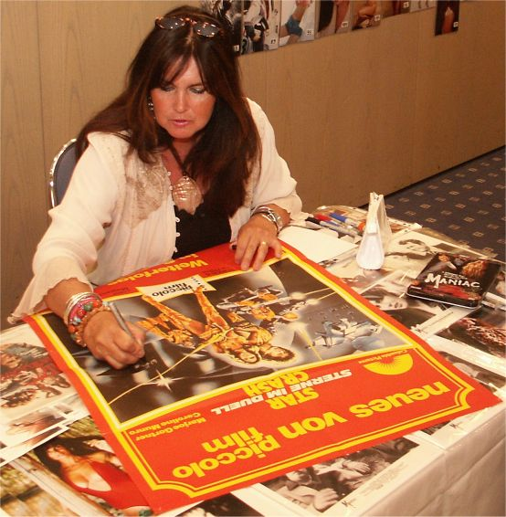 Caroline Munro en un acto reciente firmando un cartel de Star Crash