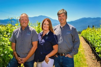 2Hawk Vineyard and Winery Team Ross Allen, Jen Allen, and Kiley Evans in Vineyard with Mountain Backdrop