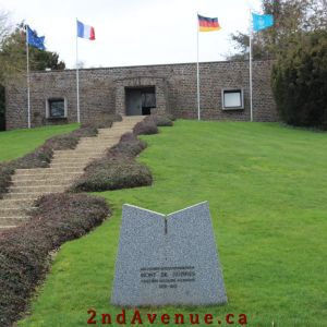 Four flags and a long set of stairs mark the German war cemetery entrance