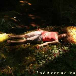 Photograph of Laura in corpse pose on a mossy forest floor