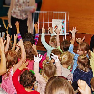 Kids raise their hands in excitement during a storytelling session at a library