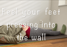 Feel your feet pressing into the wall - Laura lying on a grey yoga mat with the soles of her feet against a white wall