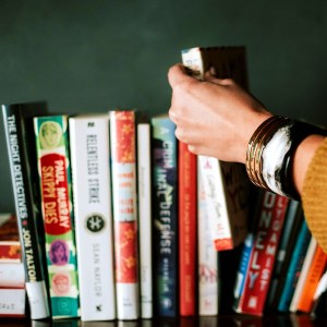 A woman's arm lifting a paperback book off a bookshelf