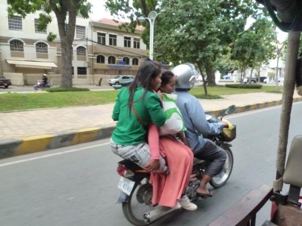 Drei Personen auf einem Motorroller. Einer jungen Frau fehlt ein Teil ihres Beins