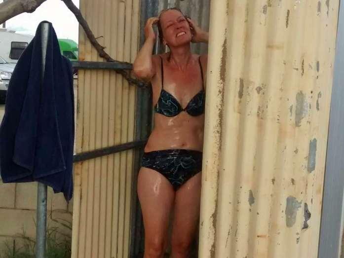 Frau im Bikini unter Dusche im Freien