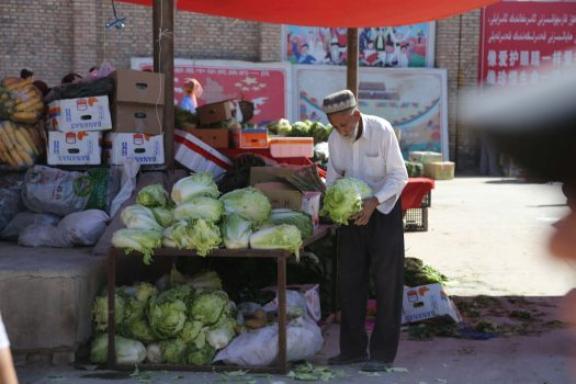 A fruit vendors lays out his produce in the Opal Village's Monday Market
