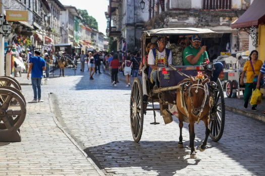 Travel down Calle Crisologo on a horse carriage