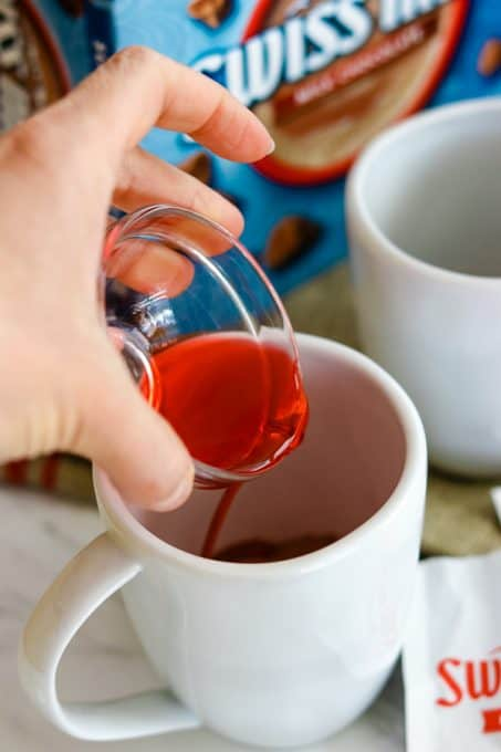 Pouring cherry juice into a cup to make Chocolate Covered Cherry Hot Chocolate.