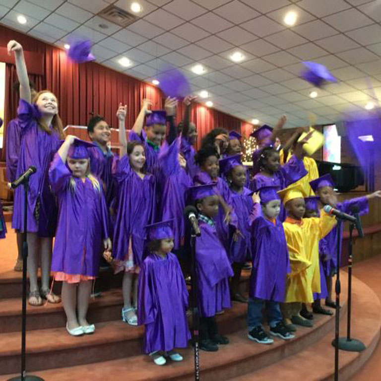 Children in graduation gowns at Charlotte Church