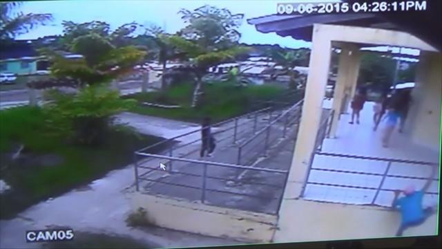 Um dos suspeitos escala grade para assaltar estudantes (Foto: Reprodução)