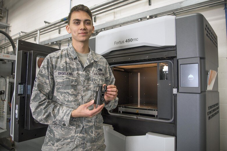 U.S. Air Force Staff Sgt. Montana Engelking, 100th Maintenance Squadron aircraft metals technology welder machinist, holds a 3D printed example at RAF Mildenhall, England [Source:  U.S. Air Force ]