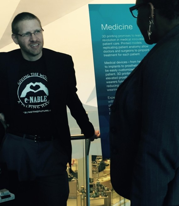 Jeremy Simon chats with a visitor to the e-NABLE table at a conference in downtown Chicago.