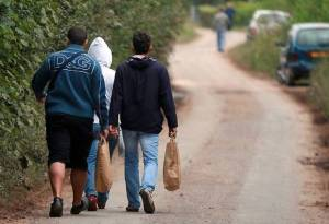 Farm workers walking through country lanes with their shopping