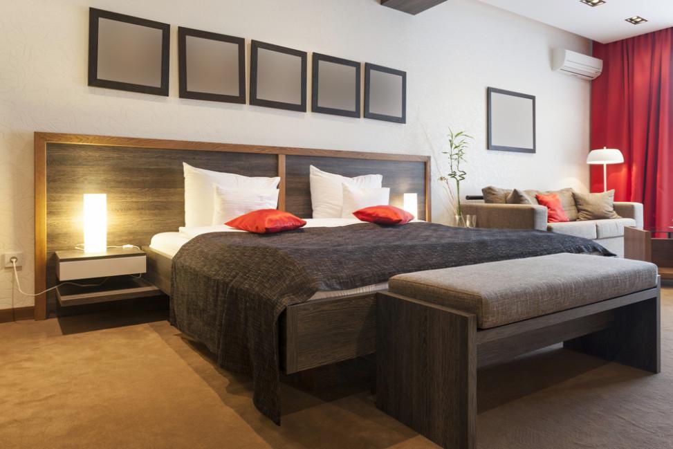 Dormitorio con suelo de moqueta y colores marrones y rojos