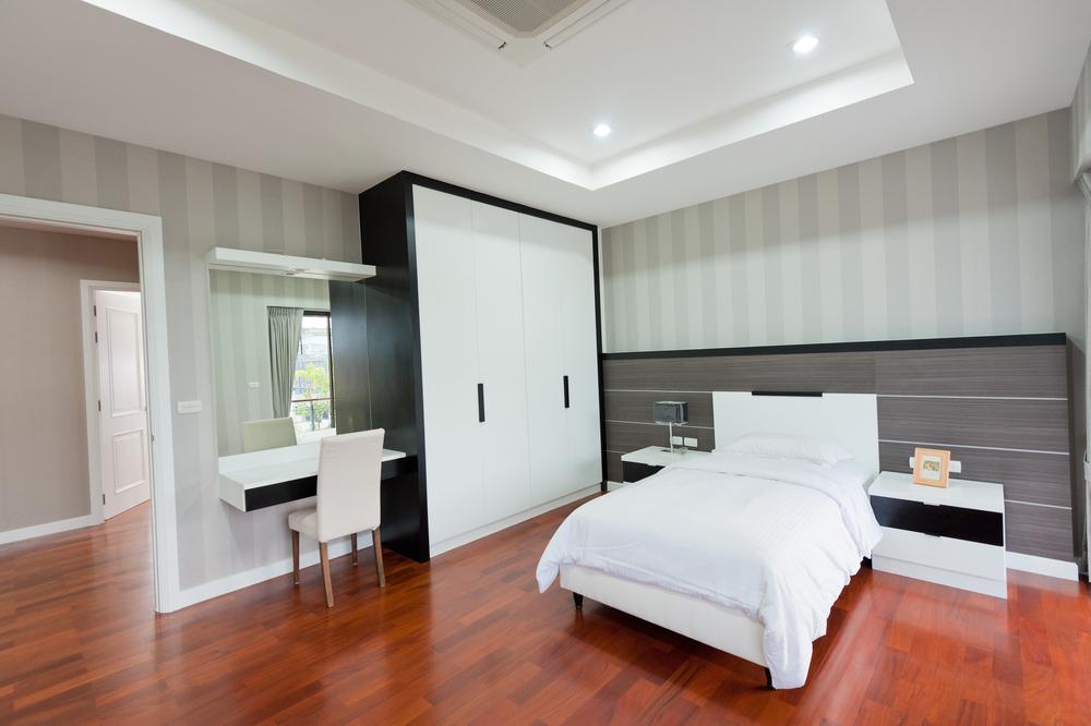 Dormitorio con suelo de parquet y muebles blancos y negros